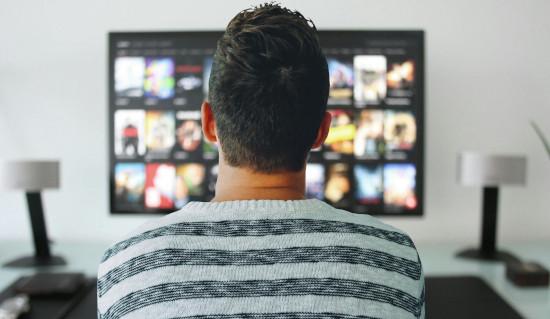 migliori app per smart tv, uomo guarda applicazioni su televisore